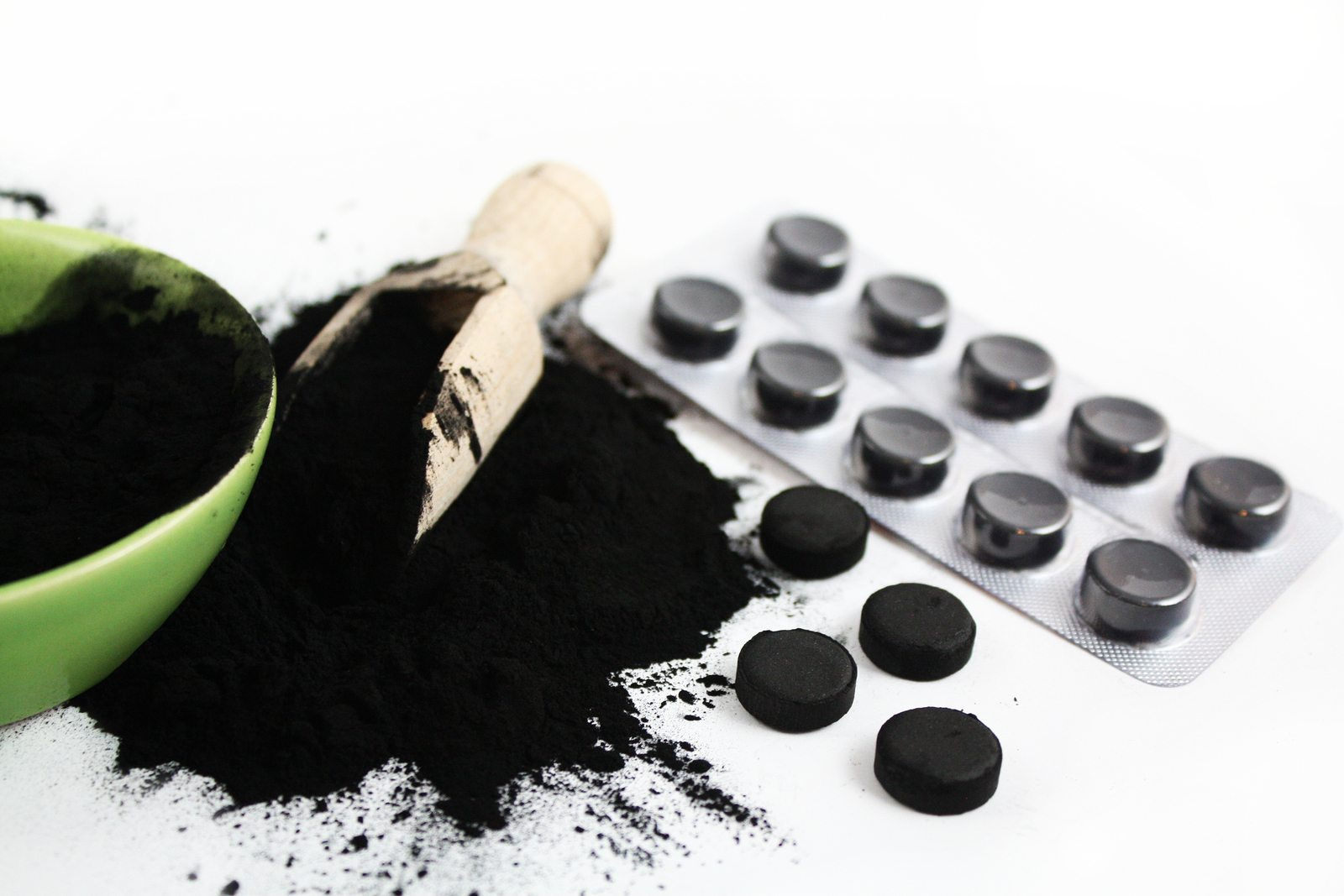 Activated charcoal powder and pills plate isolated on white healthy lifestyle concept
