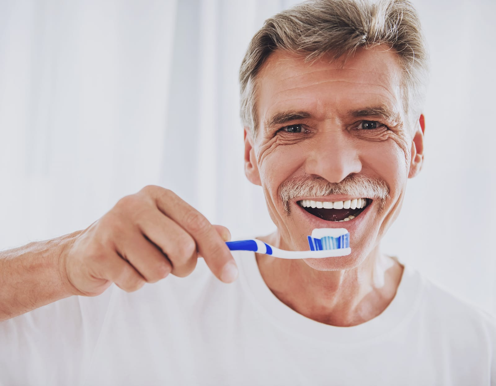 Close up. Senior Man Brushing Teeth in Bathroom. Morning Routine. Healthcare Roncepts. Elder Person at Home. Smiling Man. White Teeth. Smiling Grandfather. Dental Hygiene Concepts.