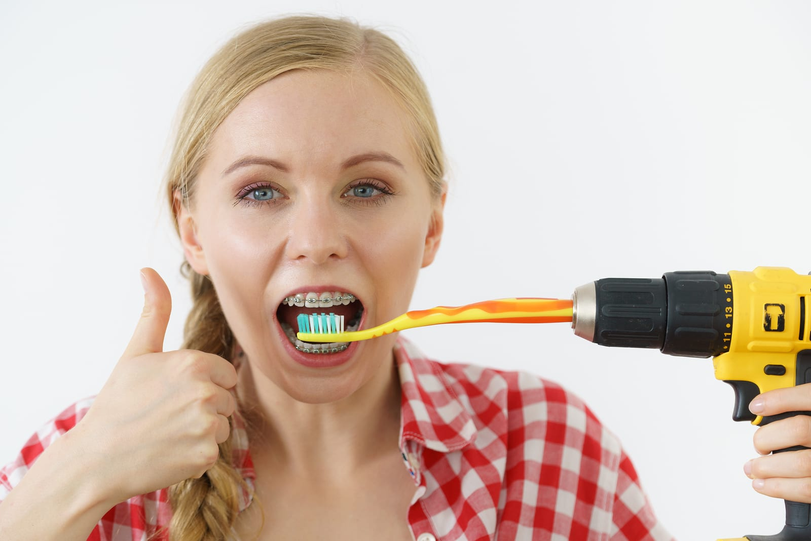 teenage girl with braces about to brush teeth with toothbrush attached to drill