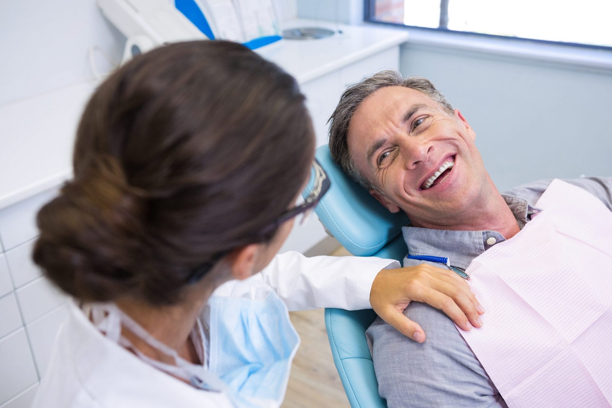 Happy patient sitting on chair while looking at dentist in medical clinic