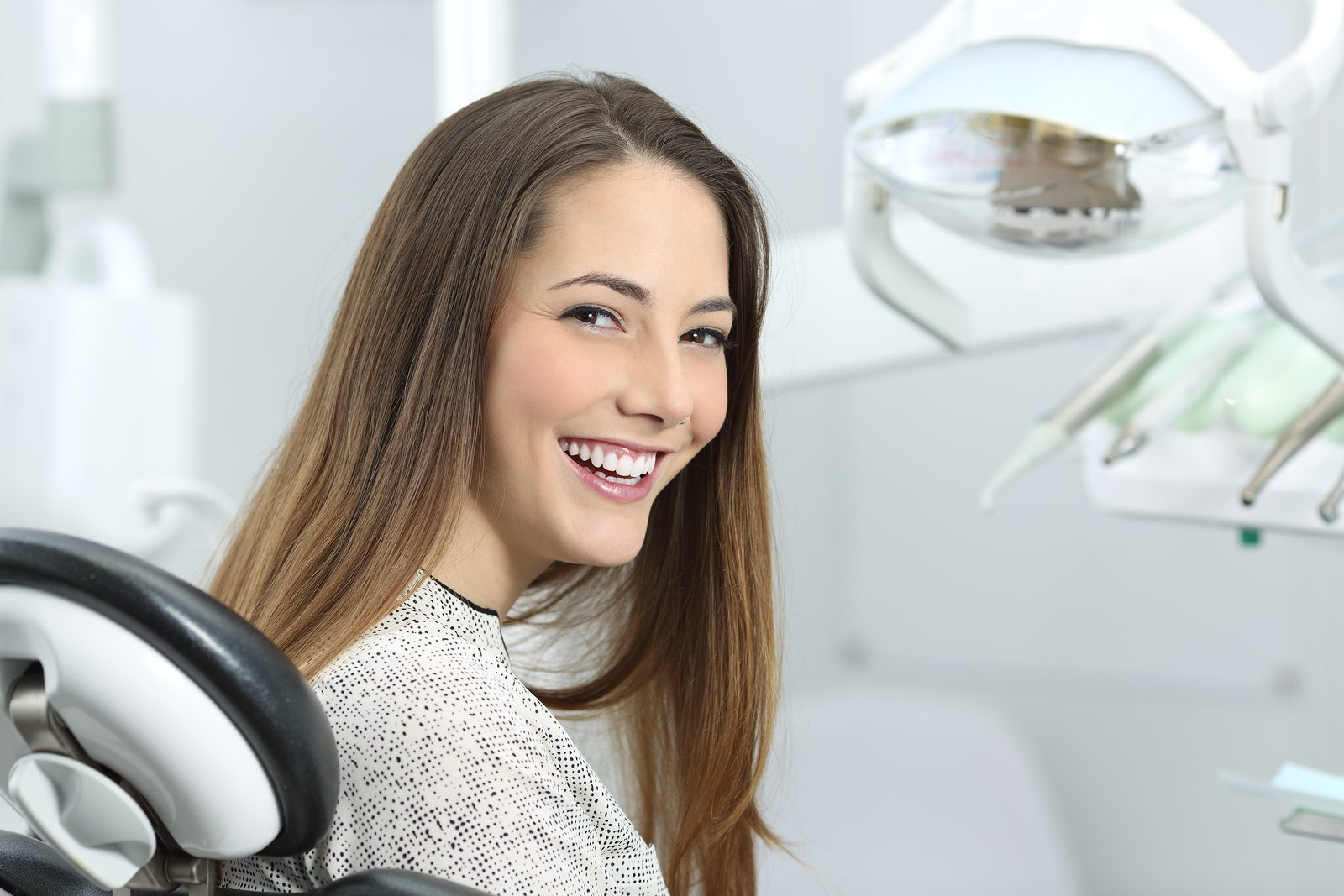 Satisfied dentist patient showing her perfect smile after treatment in a clinic box with medical equipment in the background