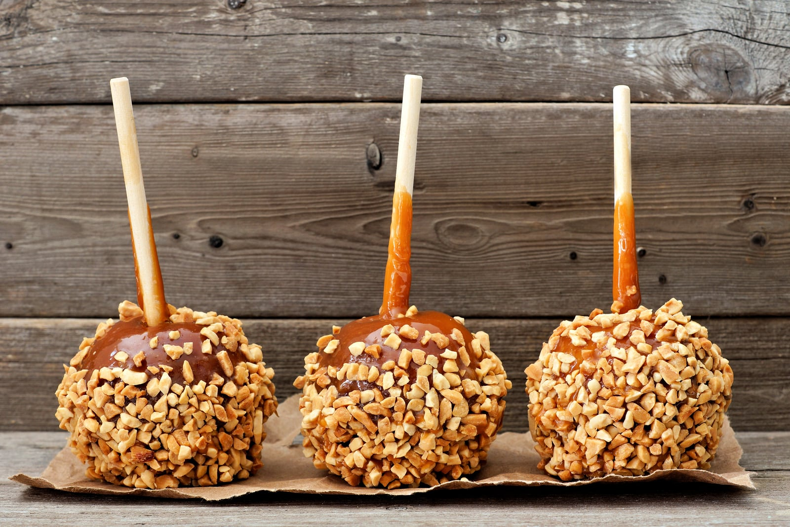 Three festive caramel apples with nuts against a rustic wood background