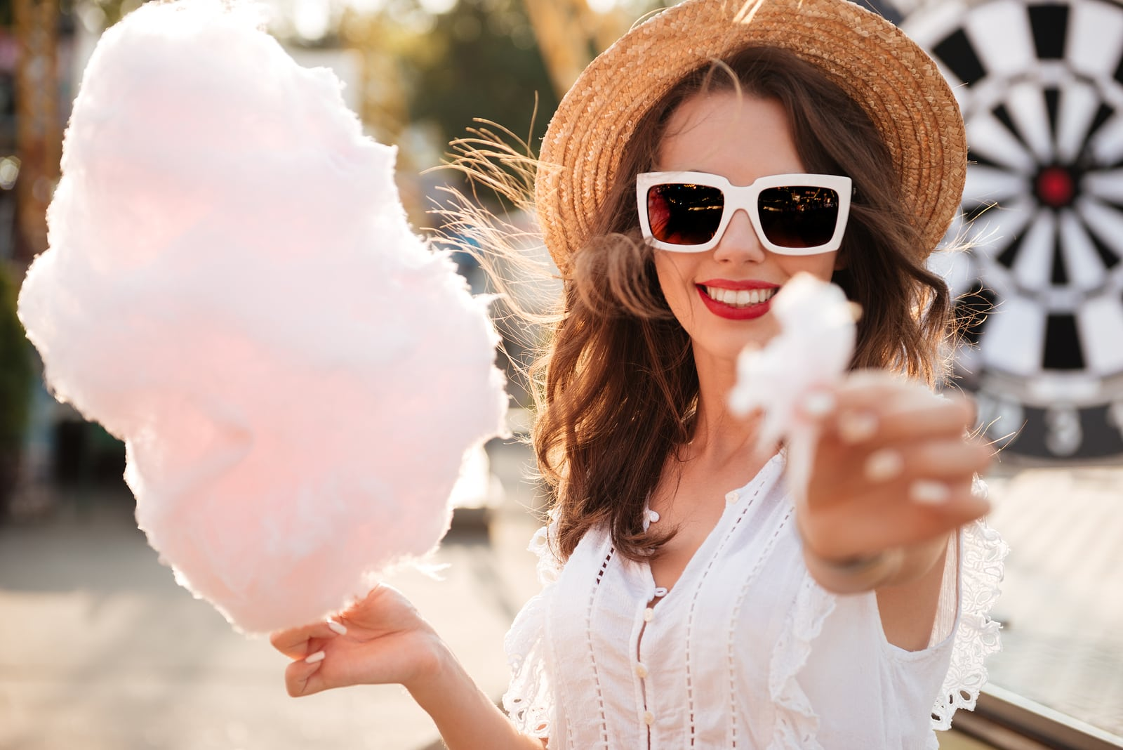 Close up portrait of a pretty young girl in sunglasses eating cotton candy at amusement park