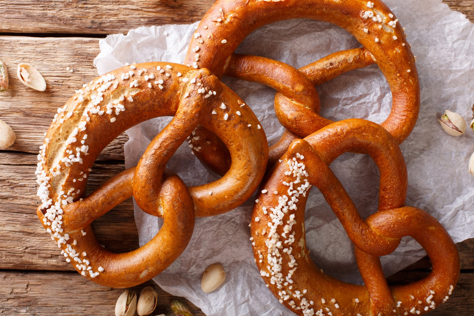 Freshly baked soft pretzel with generous sprinkling of coarse salt close-up on the table. horizontal view from above