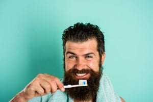 A young bearded man happily brushes his teeth to help prevent the onset of tooth decay and other dental hygiene issues.
