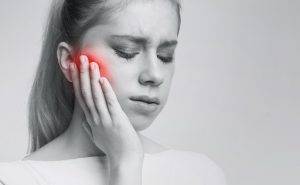 A woman clutches her cheek in pain as a result of a toothache.