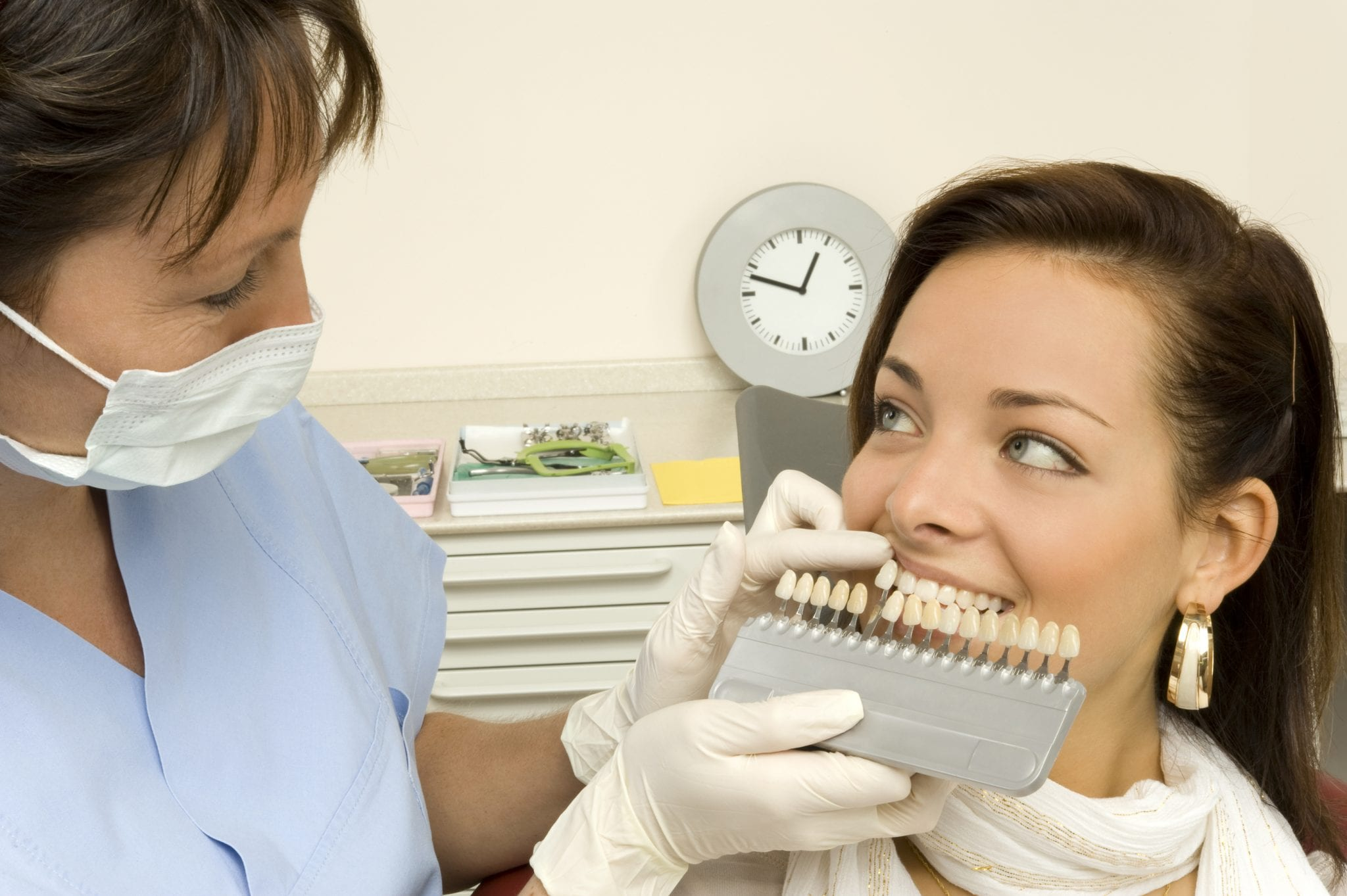 a dentist searches the correct shade of teeth for a female patient