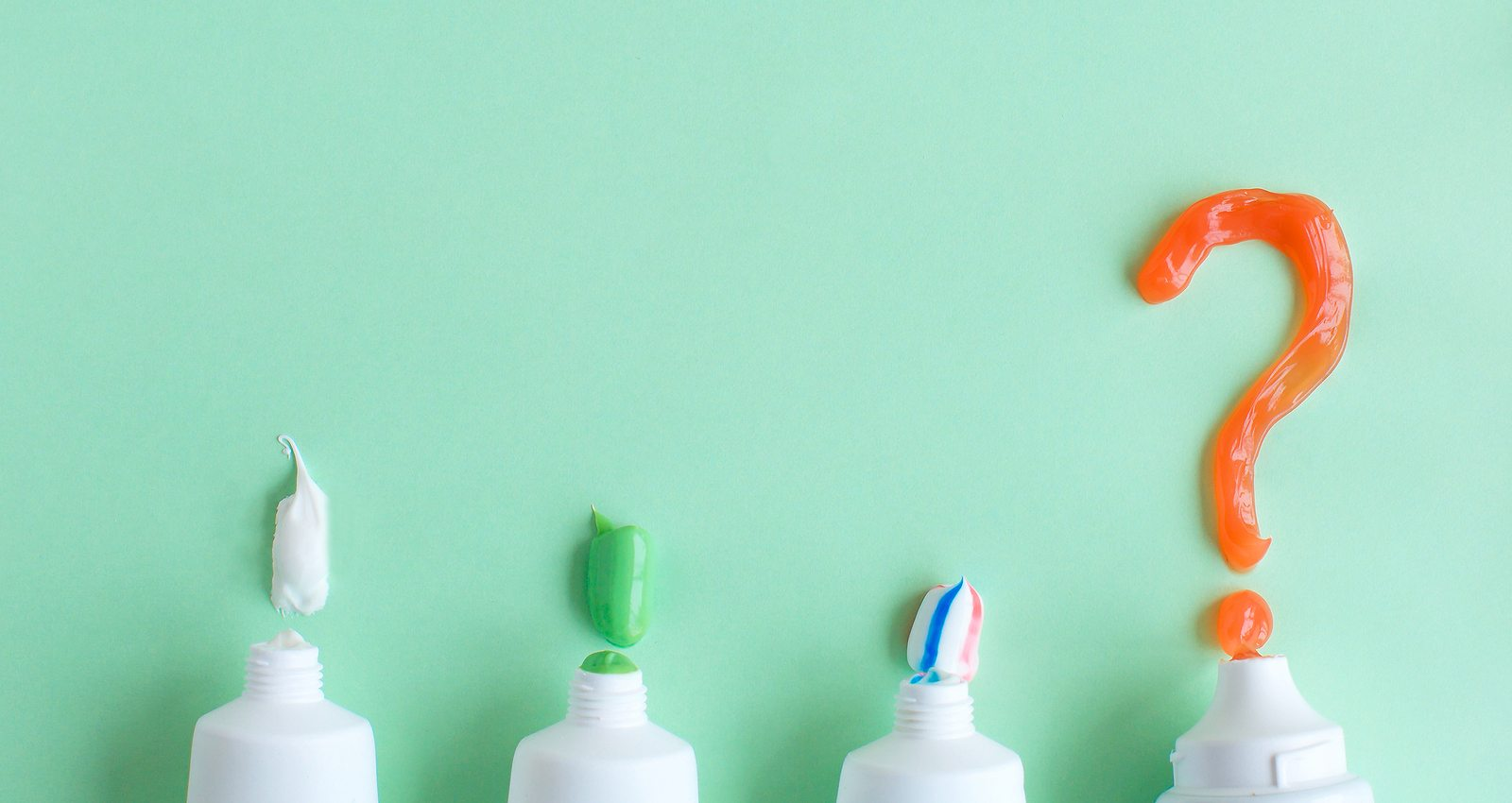 Toothpaste lies on a green background and a question mark. Choice of toothpaste. The concept of dentistry and health. Free space for copying.